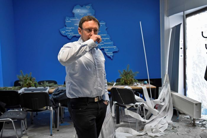 A man wearing a blue button-up shirt and black trousers puts his hand to his mouth while his office has debris from explosion.