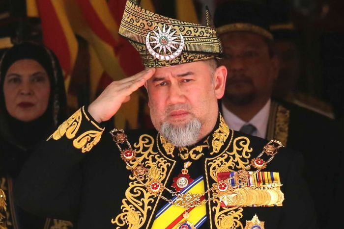 The former Malaysian sultan wearing a traditional outfit and saluting.