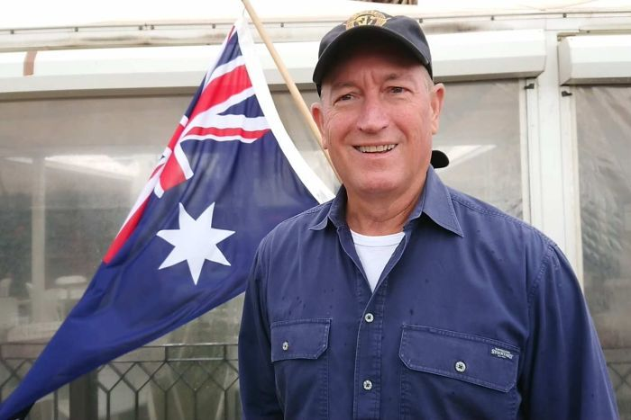 A close up shot of Fraser Anning with an Australian flag in the background