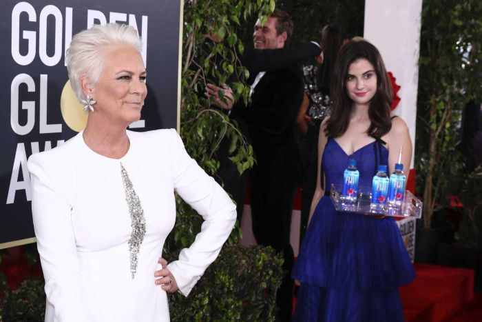 A woman holding a tray of water bottles stands in the background of a photo of Jamie Lee Curtis