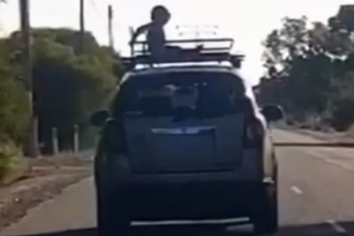 A grainy screenshot of a child sitting on a roof rack on the top of a car as it drives down a street.