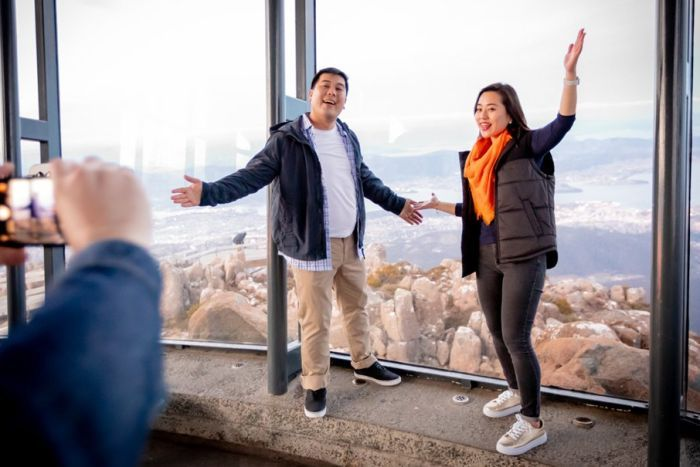 Asian tourists pose for photo at Mt Wellington summit viewing shelter, photo from Tourism Australia.