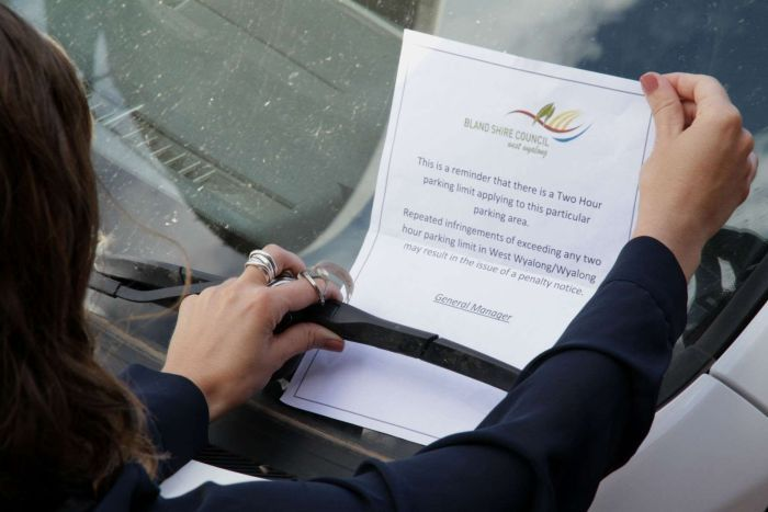 A woman pulls a parking warning from the windscreen of a white car