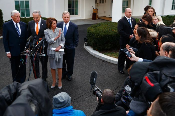Nancy Pelosi raises her hand, while Steny Hoyer, Chuck Schumer and Dick Durbin stand behind her. They are faced by the media.