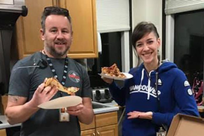 Two American air traffic controllers pose with pizza.