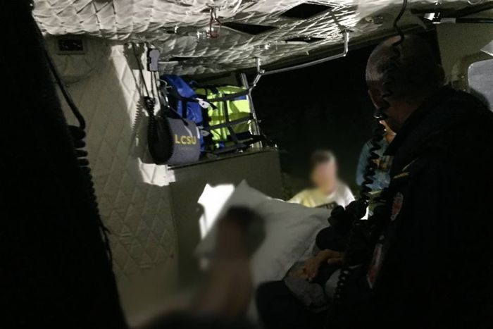 Blurred out, dark image of a boy lying against a pillow with paramedic equipment and emergency services standing in background.