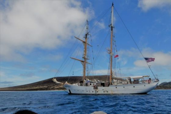 A metal-hulled boat with two masts and a US flag moored next to a low volcanic island