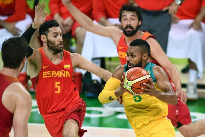 The Boomers' Patty Mills drives past Spain's Sergio Llull at the Olympics