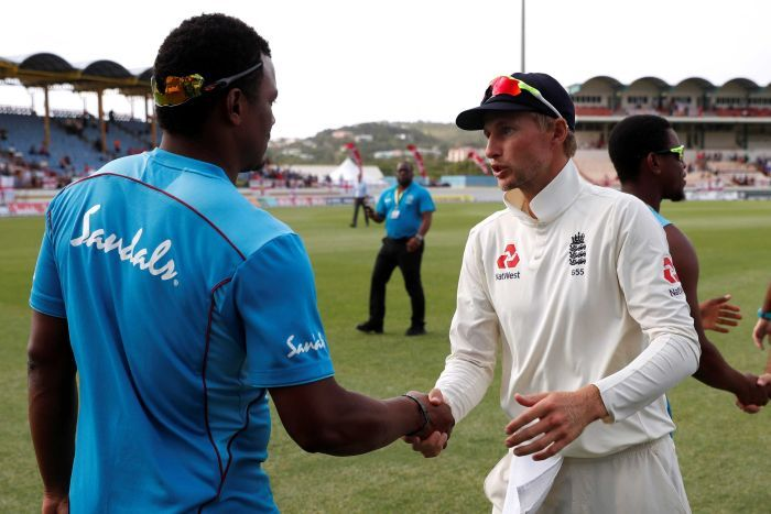 Joe Root shakes hands and speaks with Shannon Gabriel, who has his back to the camera.