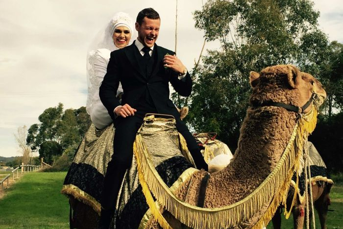 A woman in white wearing a veil sits behind a man on a camel. They are both laughing.