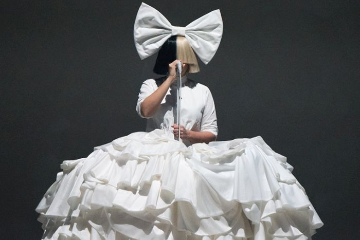 Colour photo of Sia performing on stage wearing large bow, dress and wig in 2016.