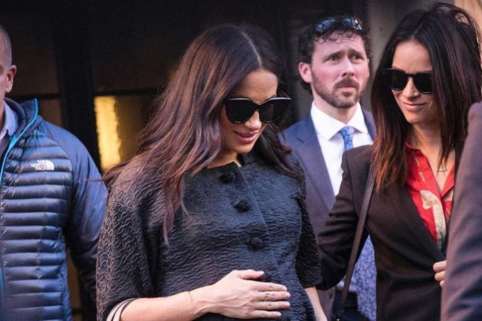 Meghan wears a black coat and sunglasses and looks down as she holds her belly with a gray bag on her arm.