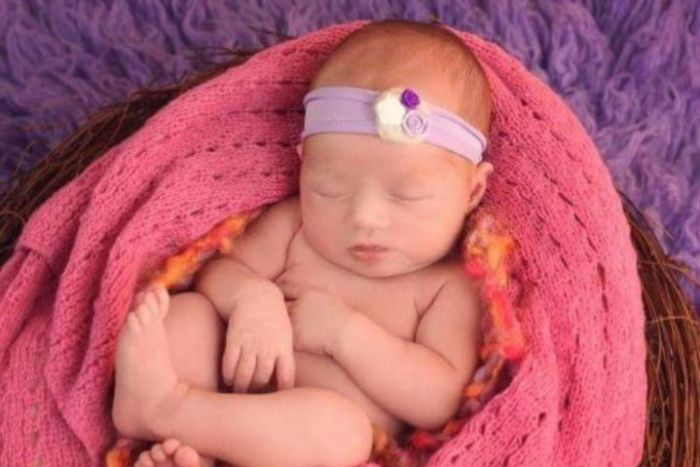 Baby Isabella asleep in a pink blanket.