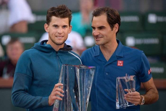 Dominic Thiem smiles while holding the Indian Wells trophy as Roger Federer looks at his opponent