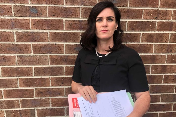 Shari Liby wears a black top and holds folders and documents.
