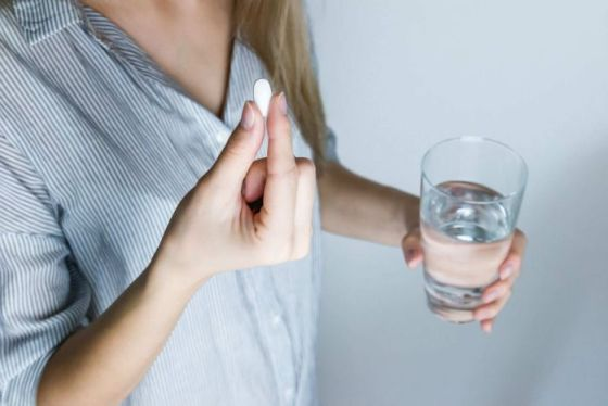 A woman holds a pill in one hand and a glass of water in the other.