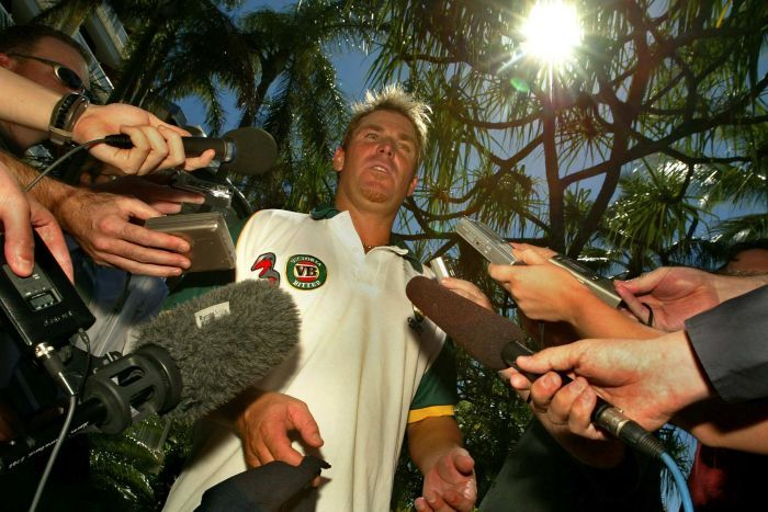 Shane Warne surrounded by journalists and cameras