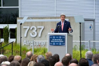 A crowd listens to a Caucasian man speaks on a lectern with the numbers '737' fastened to concrete behind him.