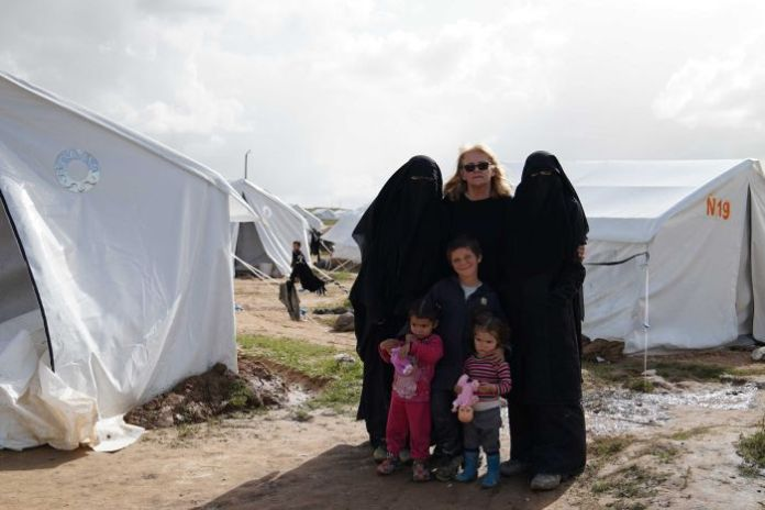 Karen Nettleton with Hoda, Zaynab, Hamzeh and two great-grandchildren in front of their ISIS refugee tent