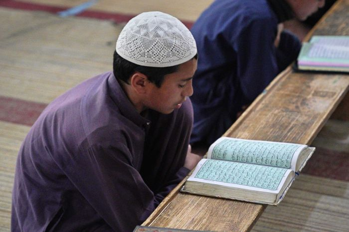 A boy crouched over a table looking at the Koran.