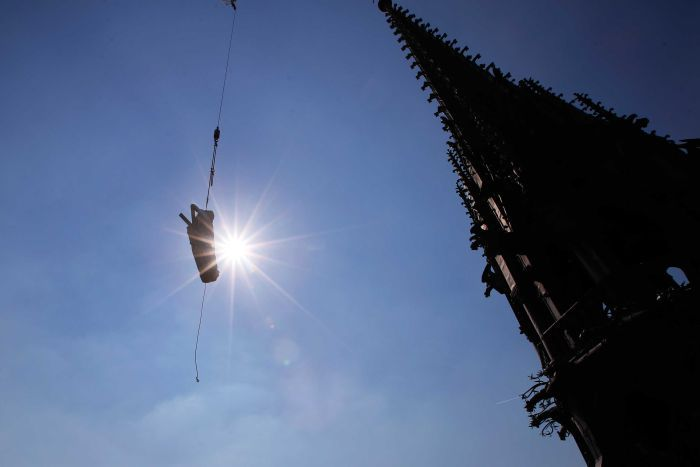 The religious statue representing St. Andrew perched atop Paris' Notre Dame Cathedral descends.