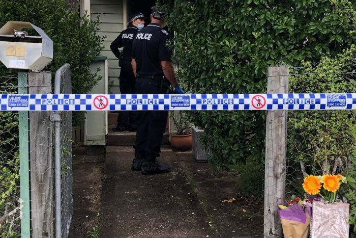 Police in front of a house with flowers at the front gate and police tape marking out a crime scene