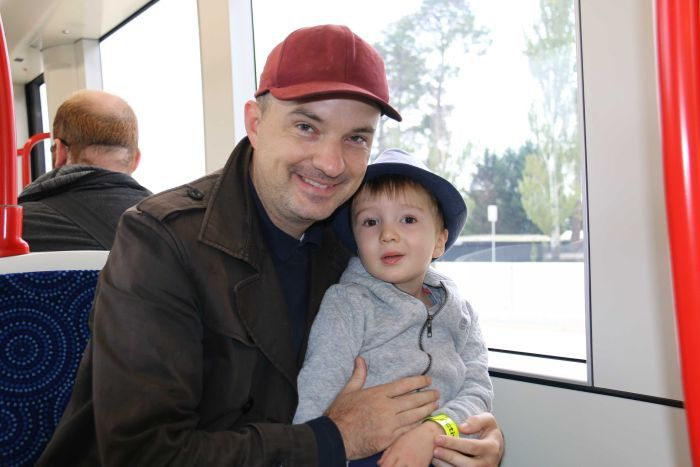 Father with his young son on his lap on a light rail vehicle.