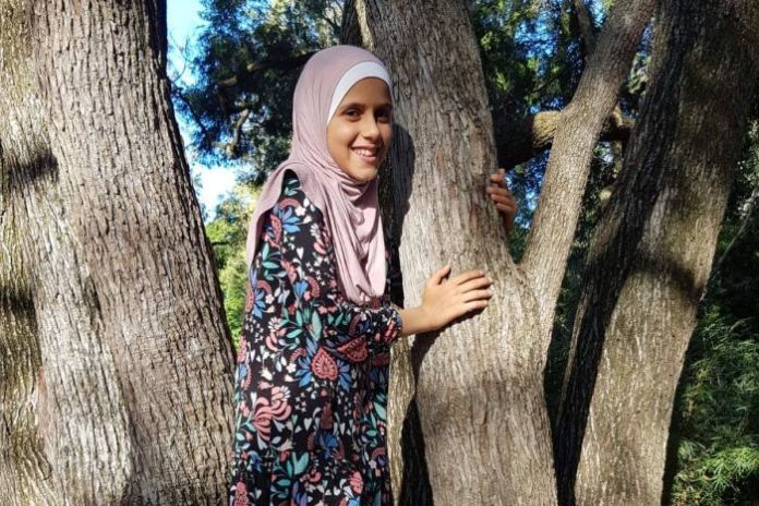 A young teenager wearing a hijab smiles as he climbs a tree