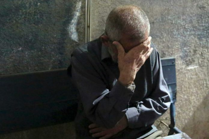 A man with short gray hair covers his eyes with a hand in pain.