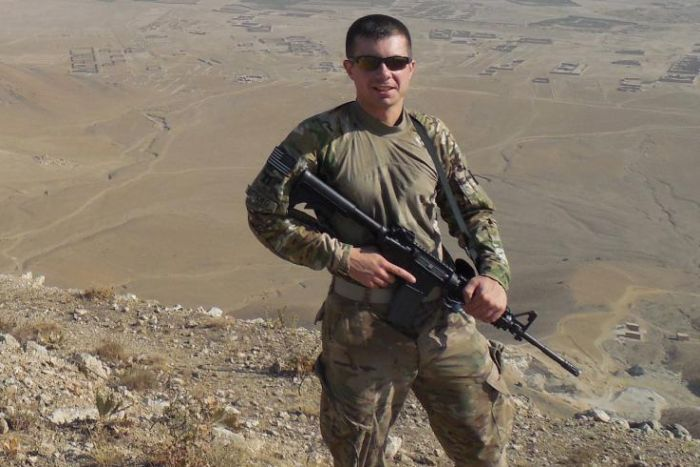Pete Buttigieg wearing army fatigues and clutching a rifle in an arid location