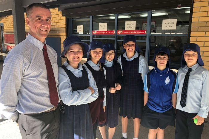 The principal Matt smiles alongside six students, including Ronan Marc, in the grounds of their school.