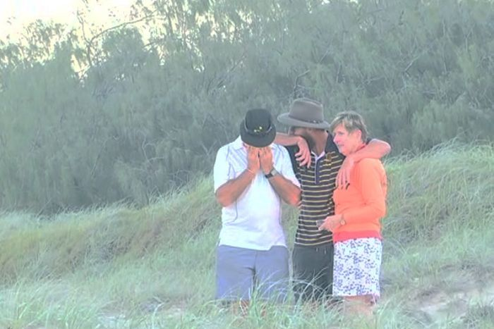 Emotional family console each other on beach.