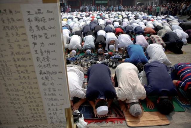 A large group of men prostrate themselves in prayer behind a board of Chinese writing.
