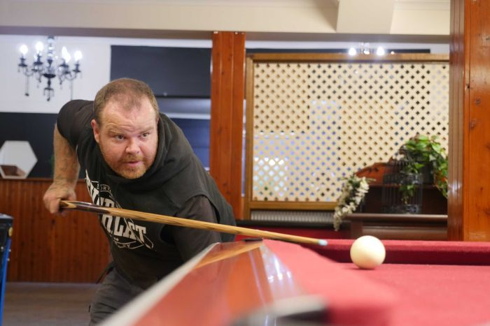 A man lines up a shot at a pool table holding the cue in his right hand, left arm pointing to the ground.