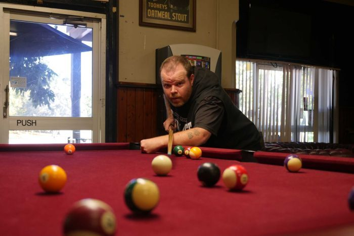 A man lines up a shot at a pool table with his right arm, using left arm folded in front of him for support