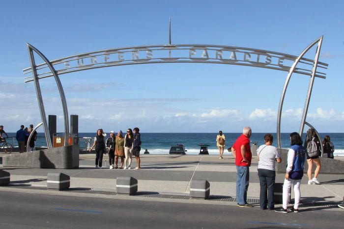 Tourists pose under the Surfers Paradise sign
