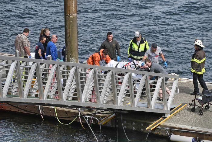 Emergency crews move a person on a stretcher towards a ramp on a seaside dock.