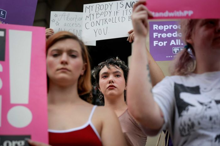 Women hold signs to protest Georgia's anti-abortion laws.