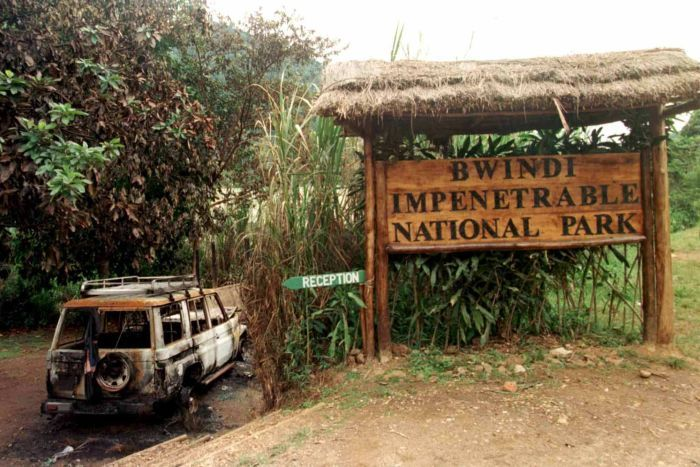The husk of a 4x4 vehicle sits outside a large wooden sign for the Bwindi Impenetrable National Park