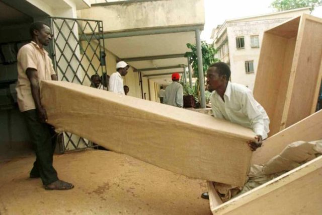 Two men load up coffins containing the bodies of tourists killed in Rwanda
