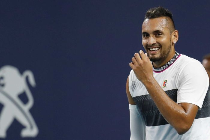 A tennis player smiles behind his raised hand on court during a match.