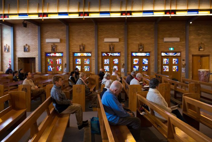 A small congregation sits in wooden pews in front of stained glass and stations of the cross.