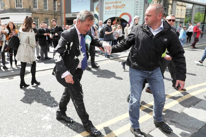 A man in a suit covered with milkshake is led away by another man holding his arm.