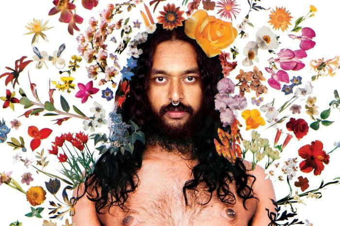 A portrait of artist Ramesh Mario Nithiyendran, standing shirtless inside an aura of flowers.