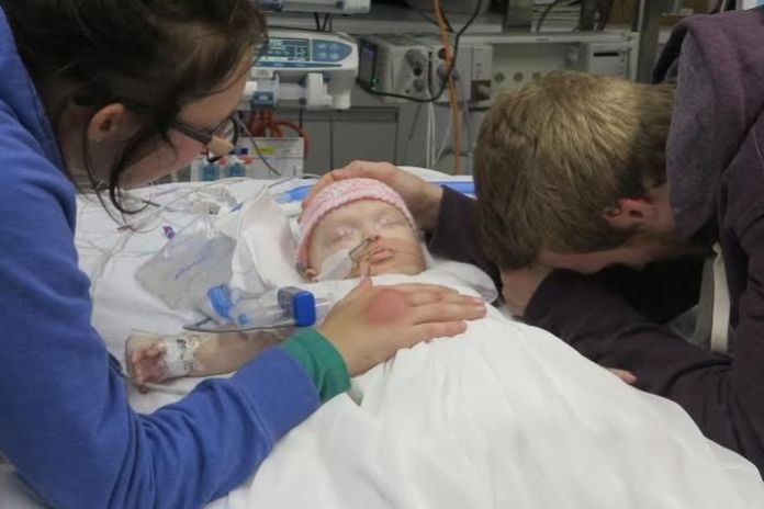 Two parents support a small child on a hospital bed.