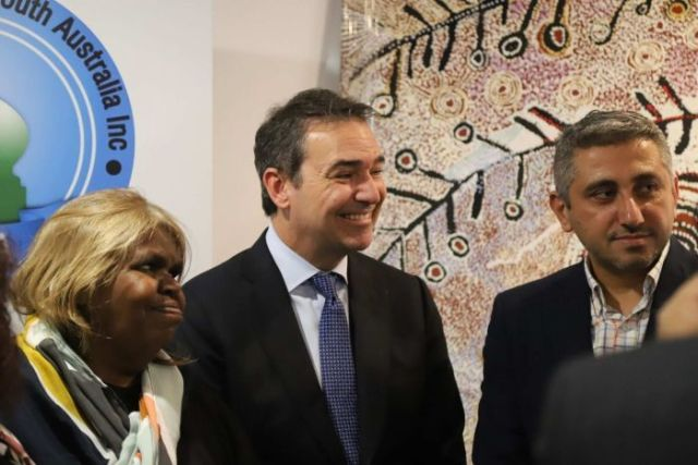 An aboriginal woman and two men smile and stand in front of an Aboriginal painting.