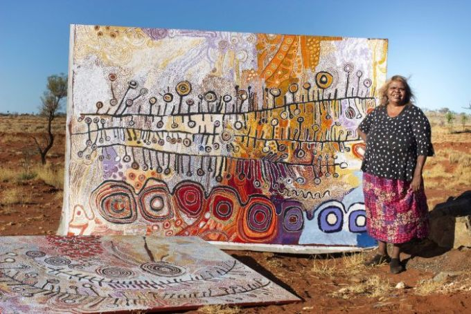 An Aboriginal woman stands in front of a large canvas in the Outback