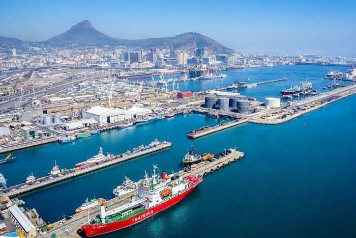 An aerial photo shows the Port of Cape Town in the foreground, and the city stretching to the mountains behind it.