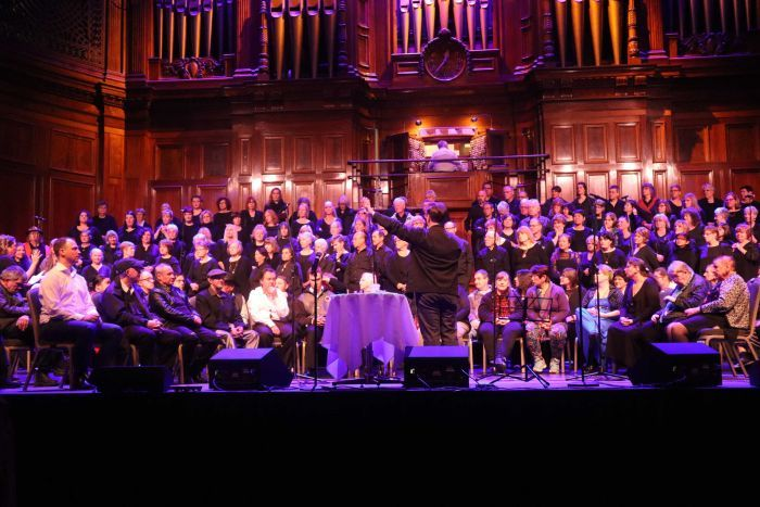 A large choir sits on a stage against a wooden backdrop