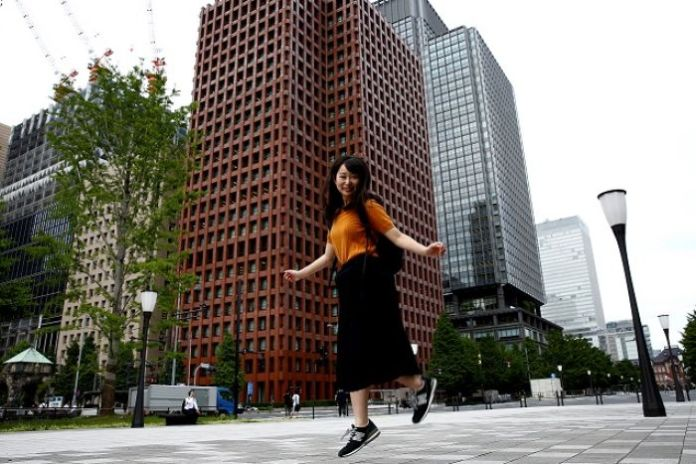 Yumi Ishikawa jumps while posing in a business district during an interview with Reuters in Tokyo.